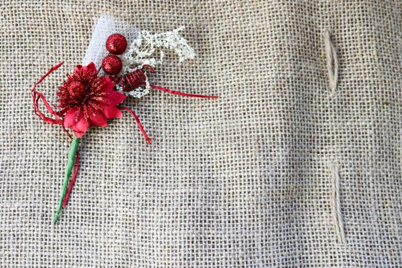 Een mooie rode kunstbloem met een groene stam op de textuur van een bruine oude linnendoek, linnen natuurlijk materiaal met ruw royalty-vrije stock foto