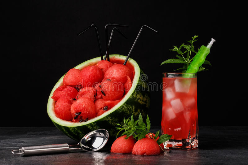 Een mooie samenstelling van watermeloenproducten op een zwarte achtergrond Rode watermeloenlepels en zoete bessendrank stock foto's