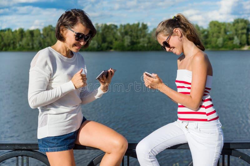 Een mooie tiener en haar mooie moeder gebruiken smartphones, stock fotografie