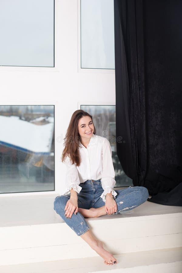 Een mooie vreugdevol glimlachende vrouw met donker haar, gekleed in vrijetijdskleding in jeans en een overhemd, bekijkt de camera stock foto