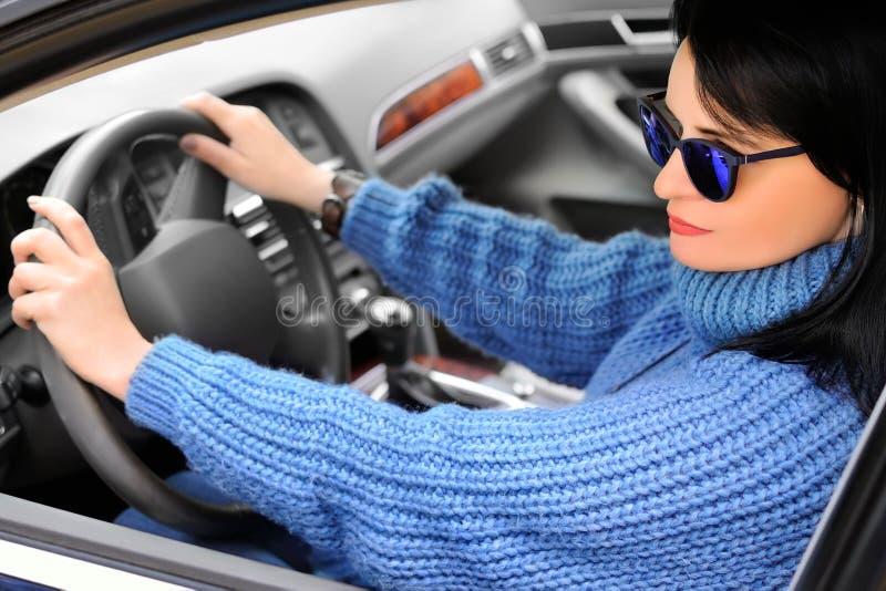 Een mooie vrij donkerbruine vrouw in een blauwe sweater en zonnebril drijft een auto stock afbeelding