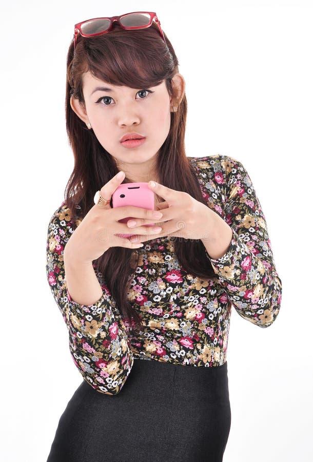Een mooie vrouw die een roze celtelefoon dragen stock afbeeldingen