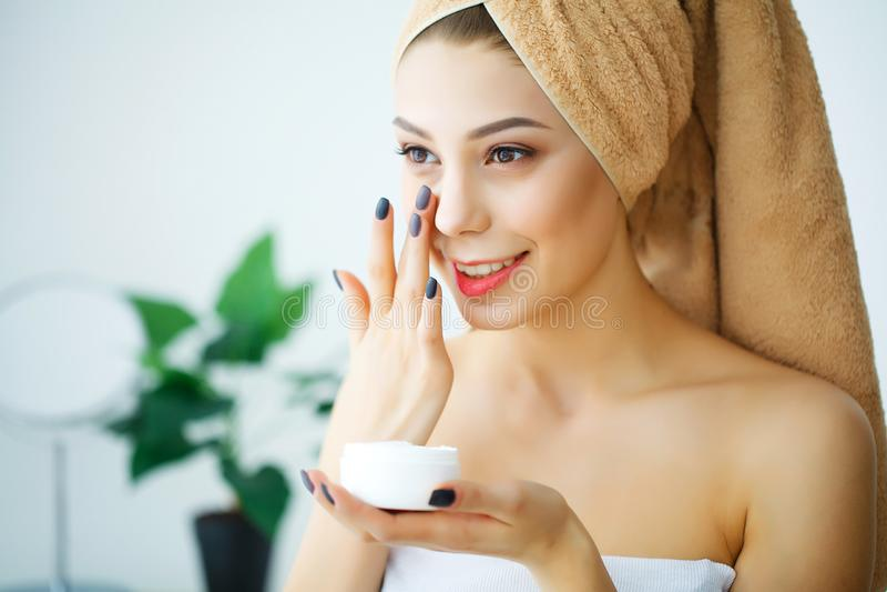 Een mooie vrouw die een een product, vochtinbrengende crème of loti van de huidzorg gebruiken stock afbeelding