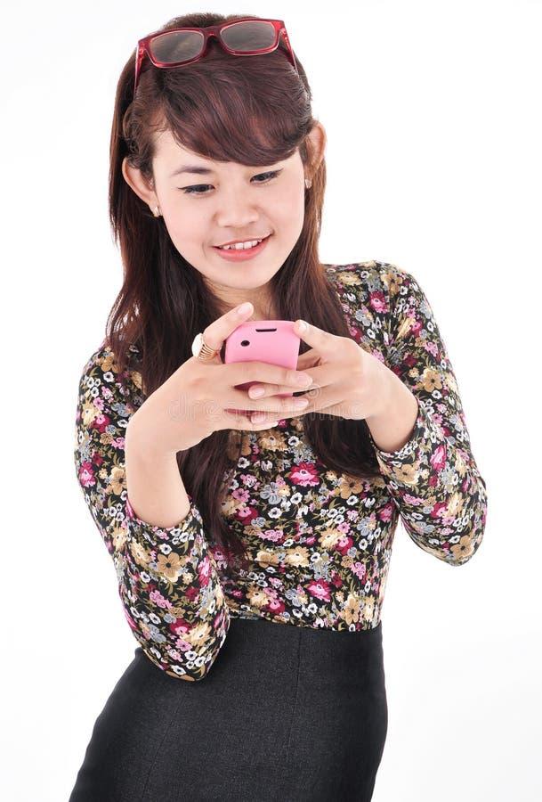 Een mooie vrouw die terwijl het dragen van een celtelefoon glimlachen stock foto