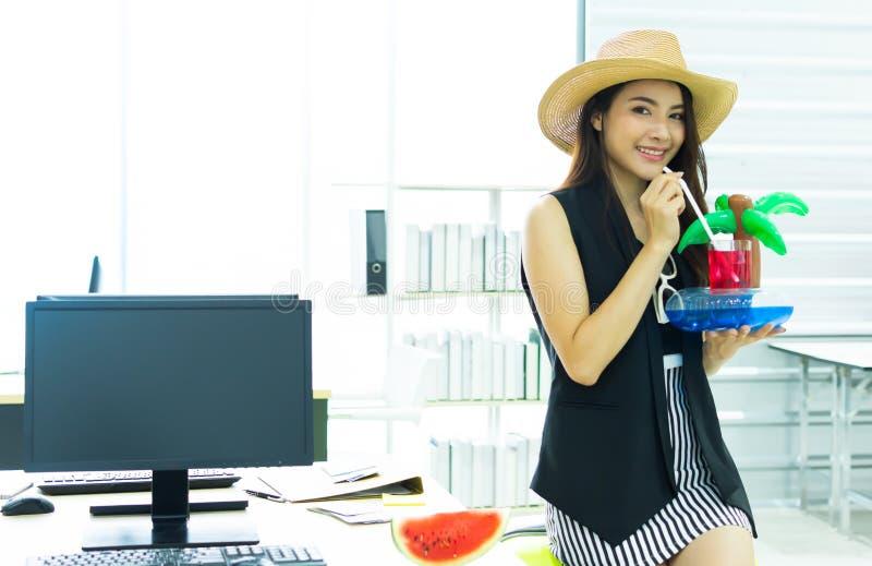 Een mooie vrouw is drinkwater in bureau stock afbeelding