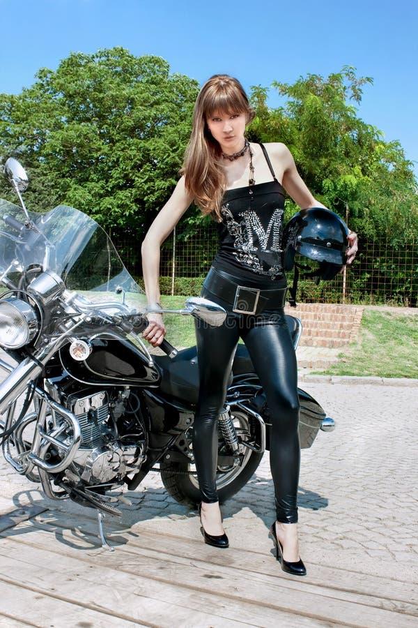 Een mooie vrouw houdt een zwarte motorfietshelm stock fotografie