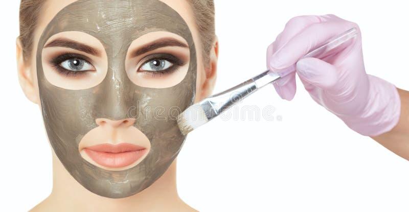 Een mooie vrouw maakt een antirimpelmasker op haar gezicht, houdt zij een katoenen bloem in haar handen stock foto's