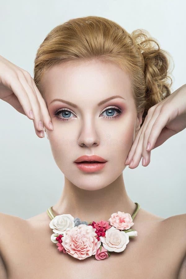 Een mooie vrouw met een halsband van bloemen stock foto's