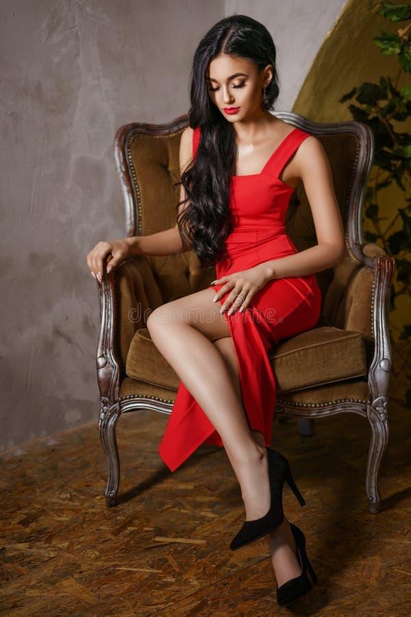 Een mooie vrouw met een rode kleding zit op een stoel, een mooie samenstelling en heldere rode lippen stock foto's