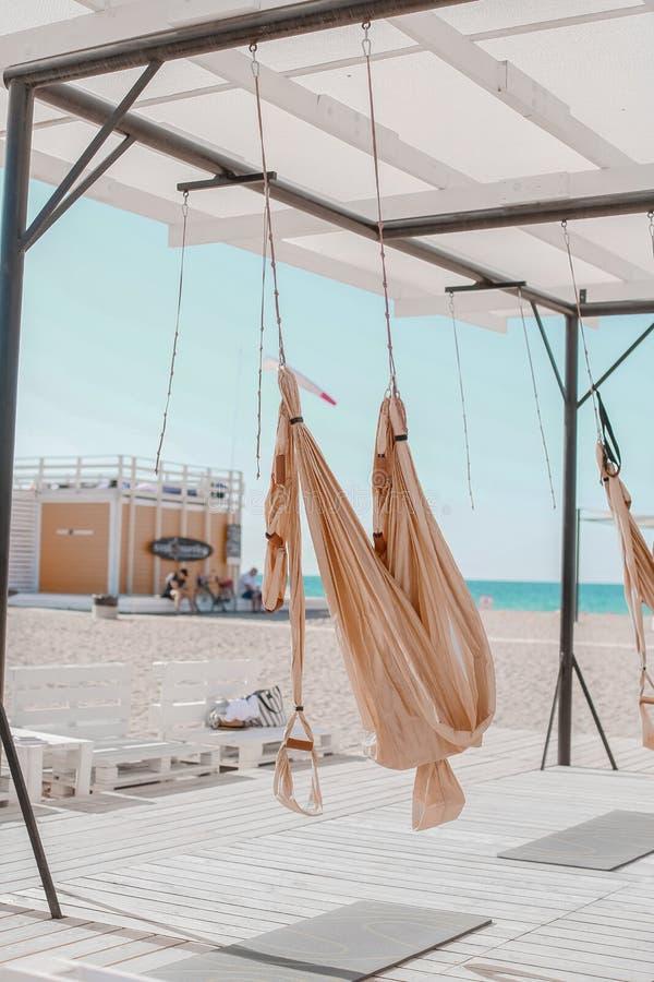 Een Mooie vrouw nam in openlucht in antigravity yoga in dienst door het overzees op het strand royalty-vrije stock foto's