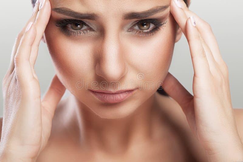 Een mooie vrouw op een grijze achtergrond, een spanning en een hoofdpijn met migrainehoofdpijnen, worstelde zij met pijn, een gro stock foto