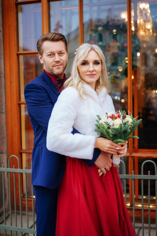 Een mooie vrouw in een rode kleding bevindt zich met een man, een bruid en een bruidegom, gelukkige jonggehuwden stock foto's