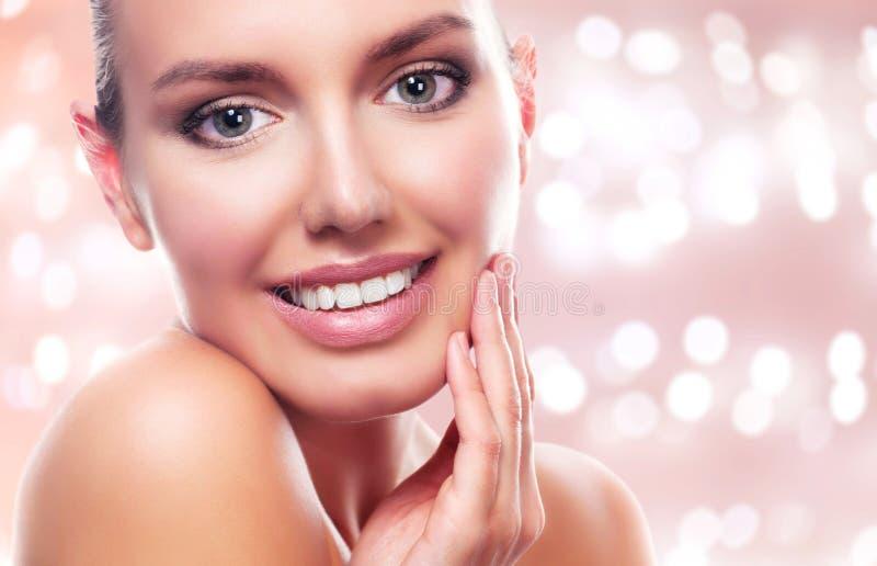 Een mooie vrouw staat een portret met een gezonde huid Mooie meid glimlacht naar je op een abstracte achtergrond met royalty-vrije stock foto
