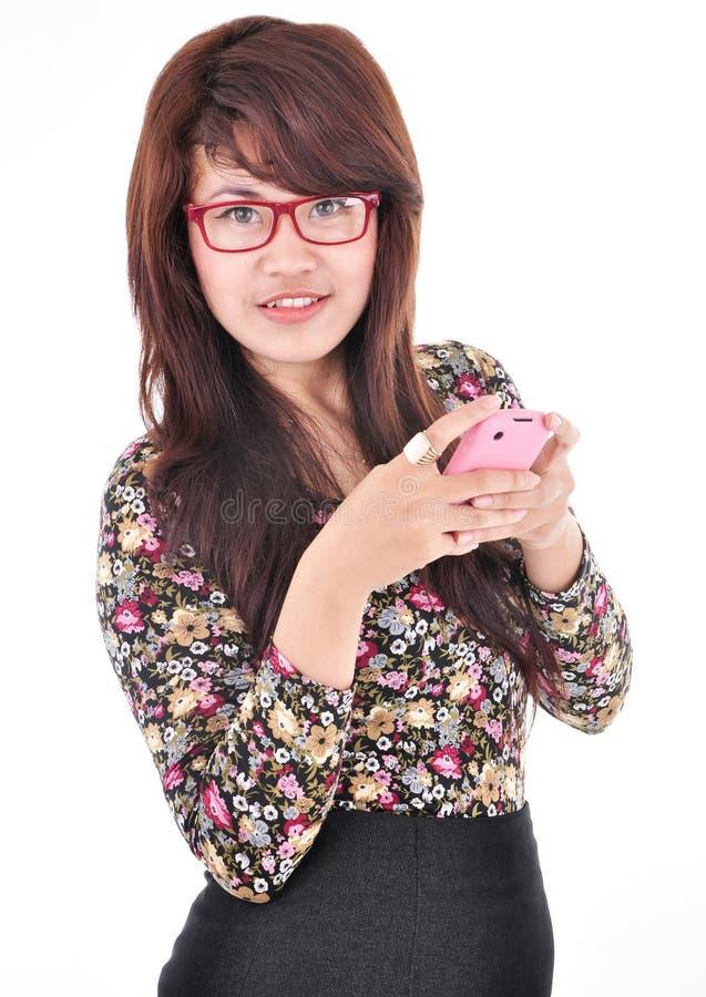 Een mooie vrouw verzendt een bericht naar de telefoon stock afbeeldingen