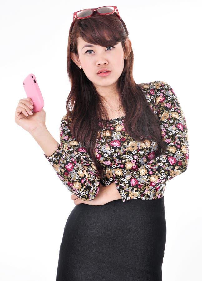 Een mooie vrouw vouwde haar wapens en draagt een celtelefoon stock foto's