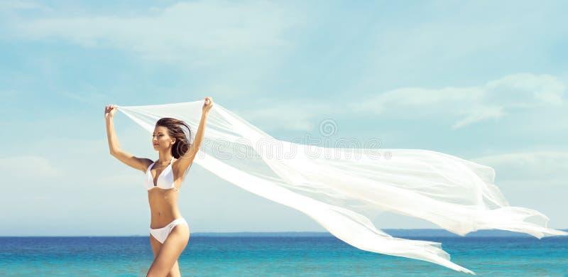 Een mooie vrouw in zwempak het stellen met een zijdedeken op Th royalty-vrije stock foto