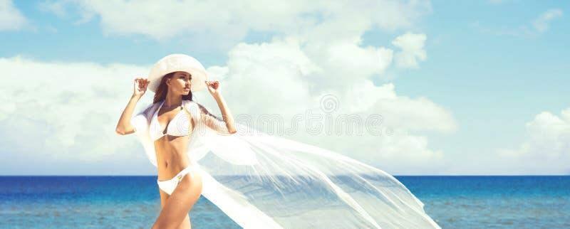Een mooie vrouw in zwempak het stellen met een zijdedeken op Th royalty-vrije stock afbeeldingen