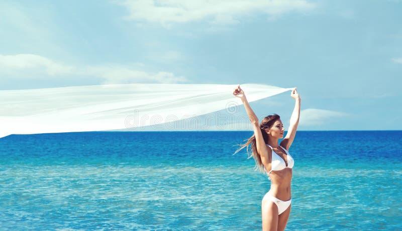 Een mooie vrouw in zwempak het stellen met een zijdedeken op Th stock foto