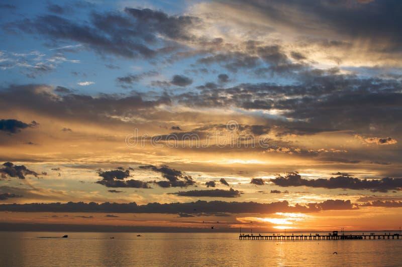 Een mooie zonsondergang die over het overzees plaatst stock afbeelding