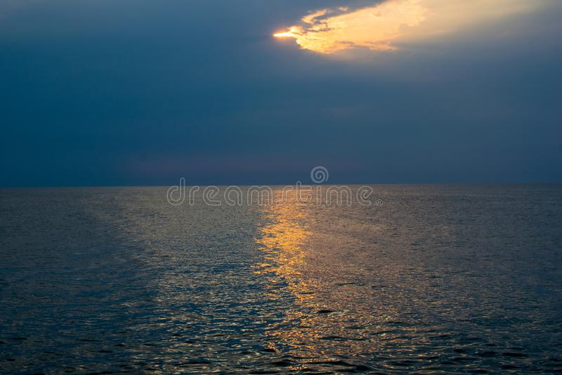 Een mooie zonsopgang op de oceaan een dramatische hemel, het onweer komt naderbij stock foto