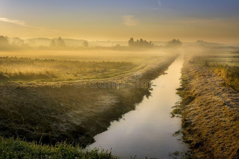 Een mooie zonsopgang over een nevelige weide en een rivier stock foto's