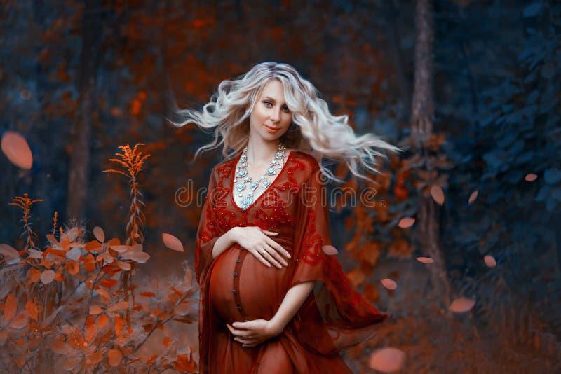 Een mooie zwangere vrouw met blond haar in lange rode kleding en glanzende halsband bevindt zich in het bos, zacht royalty-vrije stock afbeelding
