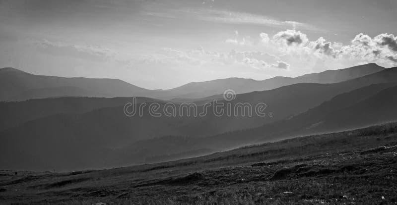 Een mooie zwart-witte die foto met valleien, heuvels en bergen in de mist worden behandeld stock fotografie