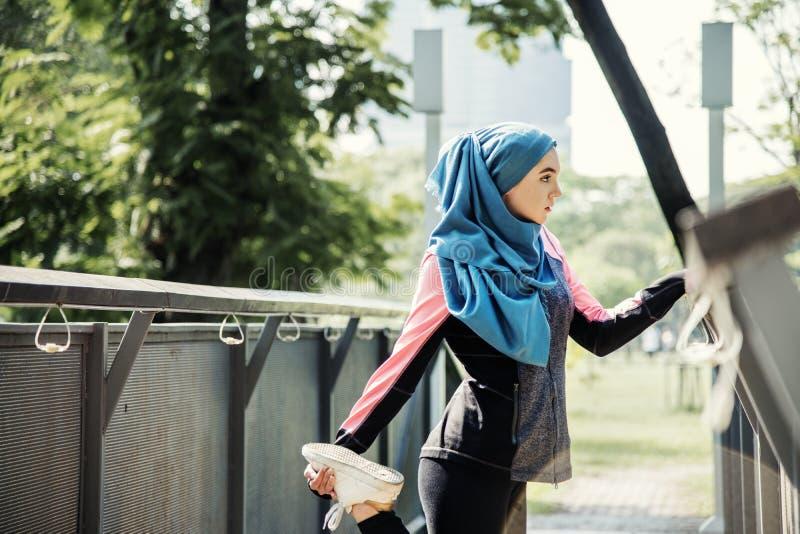 Een moslimvrouw die aan oefening opwarmen stock foto's