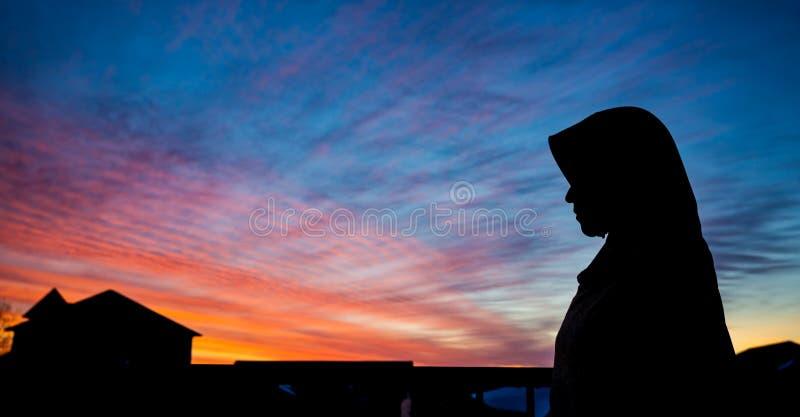 Een Moslimvrouw die uit haar flat kijken royalty-vrije stock afbeelding