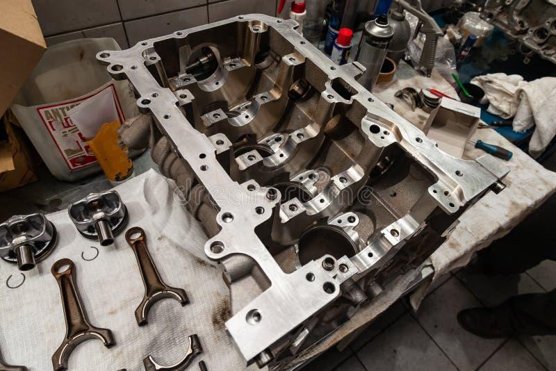 Een motor met vier cilinders veinste en verwijderde uit auto op een werkbank in een workshop van de voertuigreparatie De autoindu stock foto