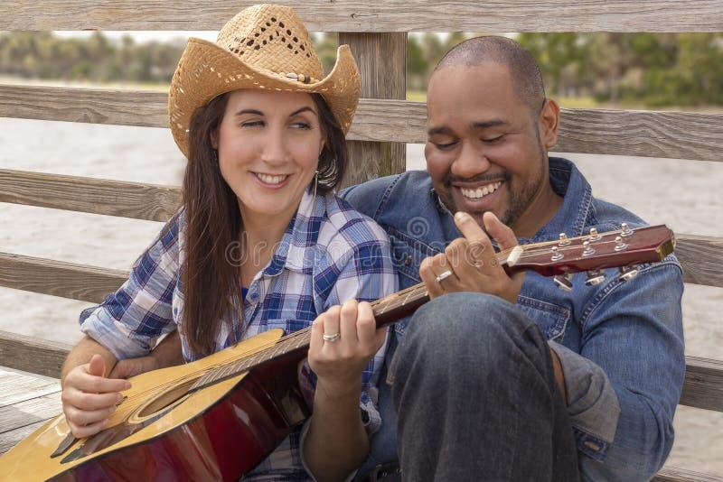 Een multiraciaal paar zit op een dek het spelen gitaar royalty-vrije stock foto