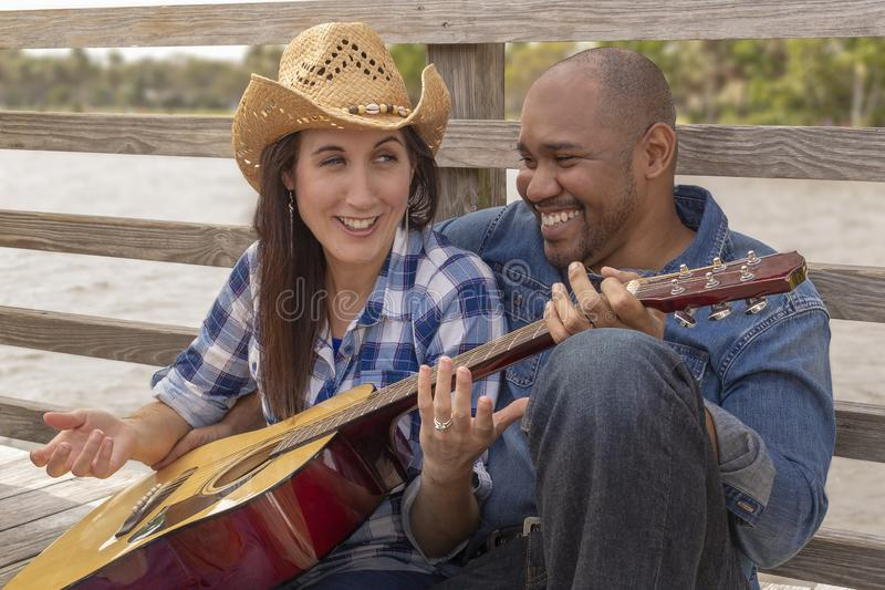 Een multiraciaal paar zit op dek luid lachen uit stock foto's