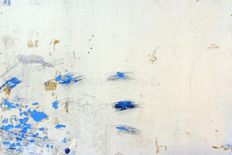 Een muur met onbegrijpelijke krassen, vlekken en scheidingen Ongebruikelijke witte achtergrond met vlekken van blauwe verf royalty-vrije stock foto's