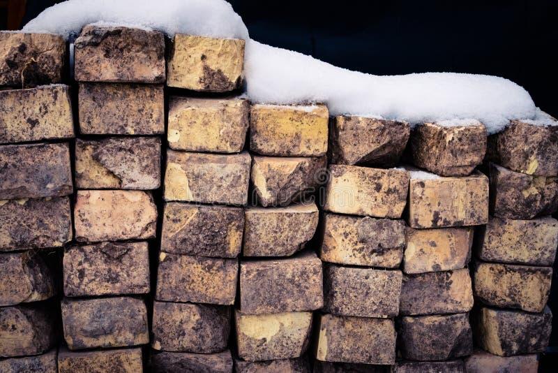 Een Muur van Bakstenen met Sneeuw op Bovenkant stock foto's
