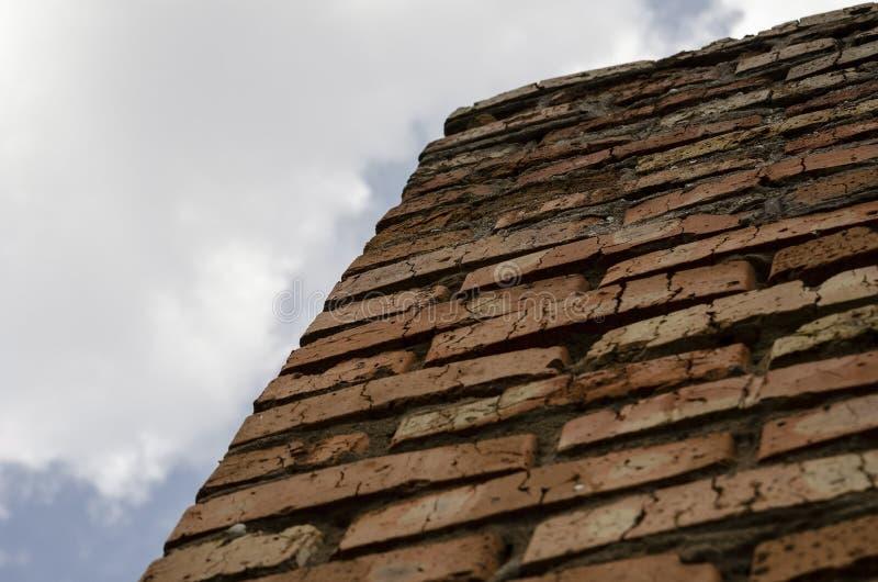 Een muur van rode baksteen tegen de hemel Onderaan omhoog Geweven Achtergrond royalty-vrije stock afbeeldingen