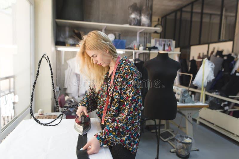 Een naaistersmeisje bevindt zich in een studio dichtbij een strijkplank en het strijken kleren werkplaats royalty-vrije stock afbeelding