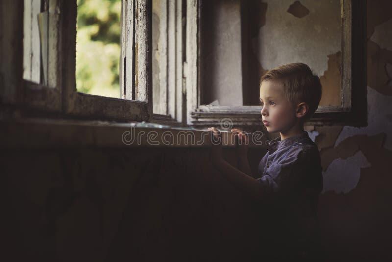 Een nadenkend, droevig kind bevindt zich door een open venster in een verlaten, oud huis stock fotografie