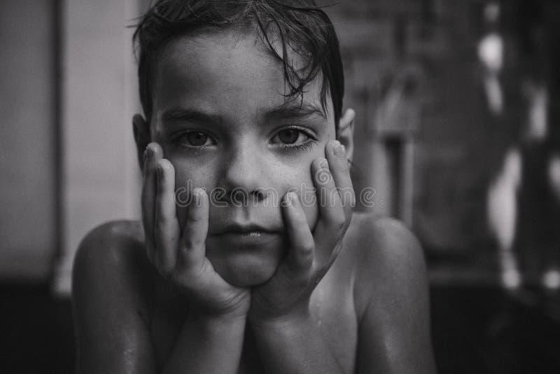Een nadenkende knappe jongen met waterdalingen op haar gezicht De Zwart-witte foto van Peking, China stock foto's