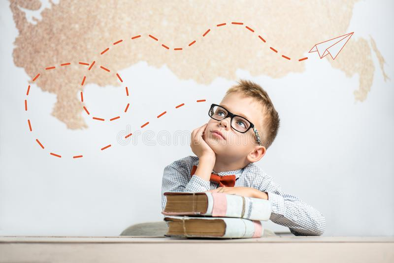 Een nadenkende schooljongen zit bij een bureau met boeken royalty-vrije stock afbeelding