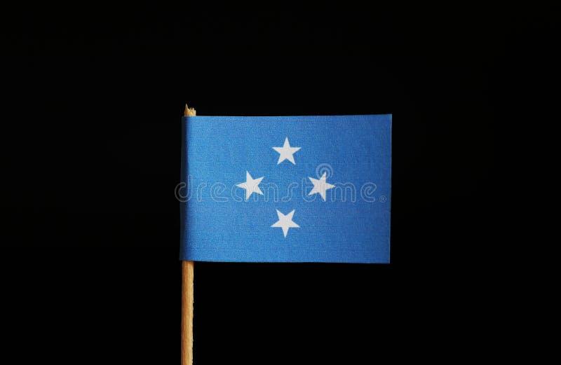 Een nationale vlag van Gefederaliseerde Staten van Micronesië op houten stok op zwarte achtergrond De federatie behoort tot Ocean stock afbeelding