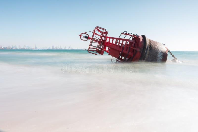 Een navigatieboei liep op het strand vast door de sterke stromen van een onweer met een lange expositie voor een zijdeeffect stock foto's