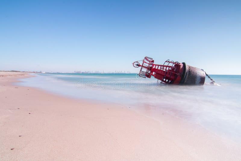 Een navigatieboei liep op het strand vast door de sterke stromen van een onweer met een lange expositie voor een zijdeeffect royalty-vrije stock fotografie