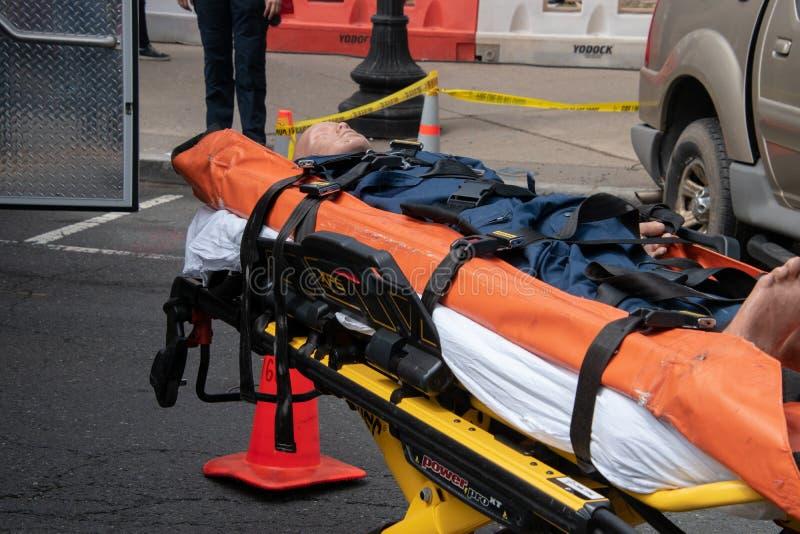 Een neerstortings proefdieledenpop op een brancard op de straat wordt getoond stock afbeelding