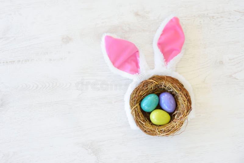 Een nest met drie gekleurde paaseieren en konijntjesoren thuis op Pasen-dag Het vieren Pasen bij de lente royalty-vrije stock foto's