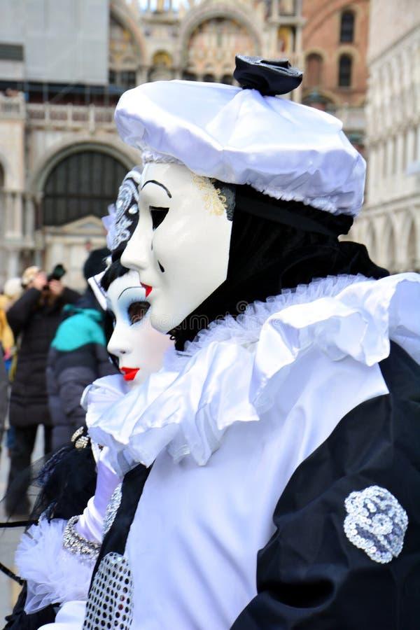Een niet geïdentificeerd paar van de mens en de vrouw dragen Pierrotkostuums met zwart-witte baret tijdens Venetië Carnaval stock afbeelding