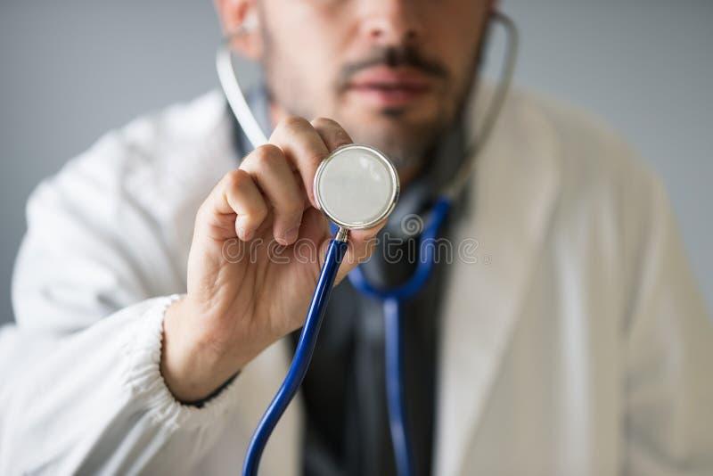Een niet geïdentificeerde arts grijpt een stethoscoop aan de camera om de patiënt te controleren stock fotografie