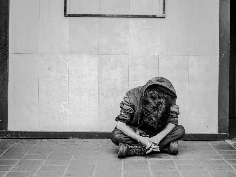 Een niet geïdentificeerde dakloze mens die voor hulp en geld bedelen Problemen van grote moderne steden stock foto
