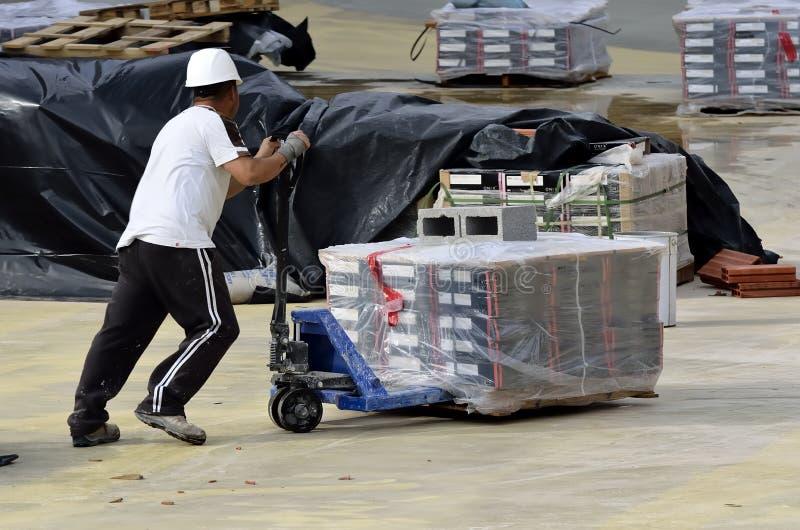 Een niet geïdentificeerde mens, die een kruiwagen in de hand dragen stock afbeelding