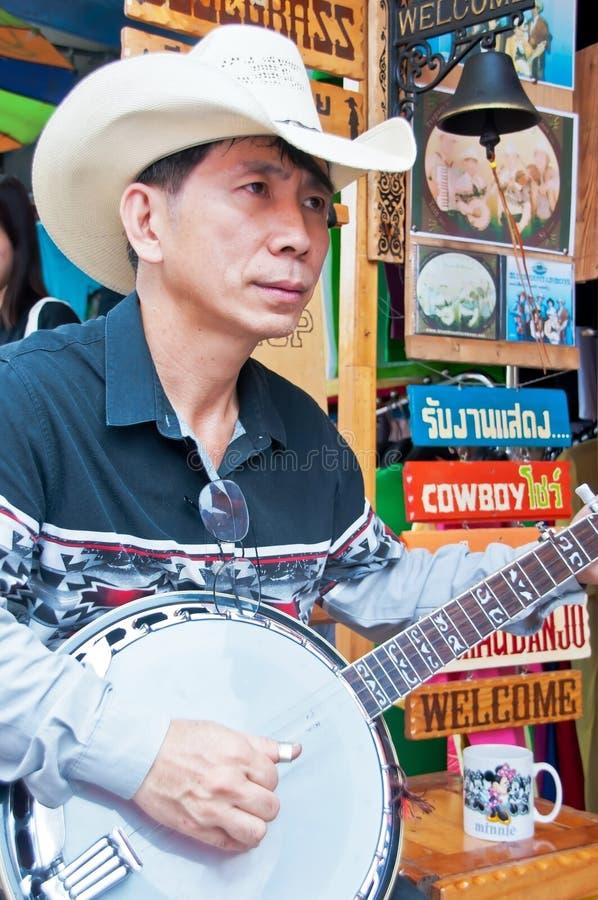 Een niet geïdentificeerde Thaise musicus presteert in Chatuchak-markt stock foto