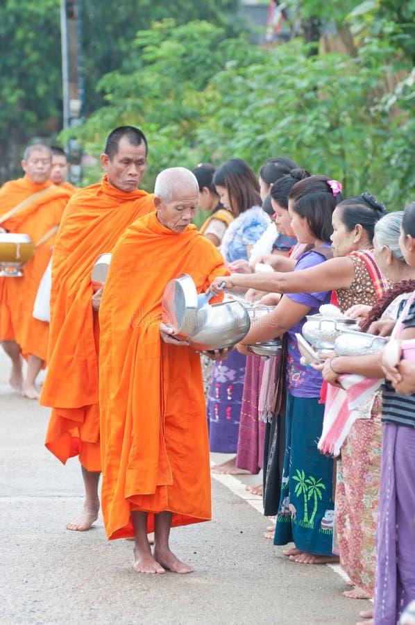 Een niet geïdentificeerde vrouw geeft voedsel aan een monnik royalty-vrije stock foto's